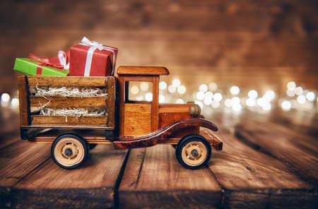 Vrolijk kerstfeest en fijne feestdagen! Geschenken dozen presenteert op speelgoedauto en Kerstmis garland lichten op oude donkere houten rustieke achtergrond. Viering concept. Stockfoto