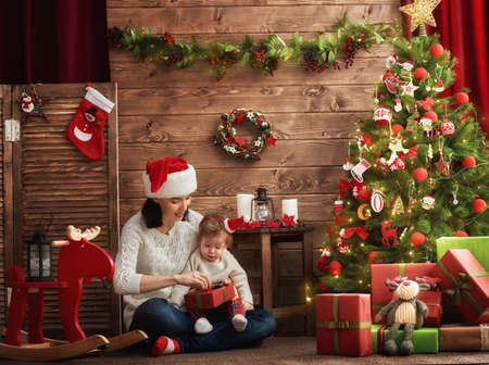baby near christmas tree: Merry Christmas and Happy Holidays! Cheerful mom and her cute daughter baby girl exchanging gifts. Parent and little child having fun near Christmas tree indoors. Loving family with presents in room. Stock Photo
