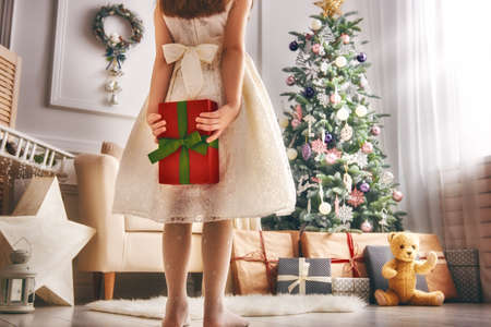 christmas gift box: Merry Christmas and Happy Holidays! Cheerful cute little child girl with present. Kid holds a gift box near Christmas tree indoors.