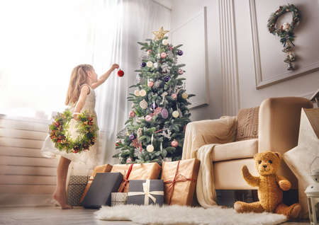 miracle tree: Merry Christmas and Happy Holidays!  Cute little child girl is decorating the Christmas tree indoors.