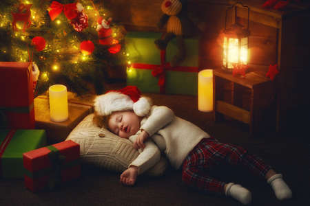 baby near christmas tree: Merry Christmas and Happy Holidays! Cute little child baby girl sleeping near Christmas tree indoors. Stock Photo