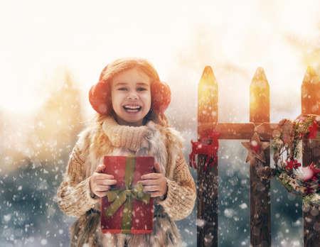 niñas jugando: Niña feliz con el regalo de Navidad en un paseo de invierno en la naturaleza Foto de archivo