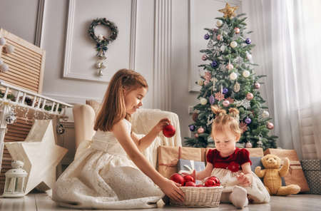 Merry Christmas and Happy Holiday! Two cute children sisters girls playing together on Christmas. Reklamní fotografie