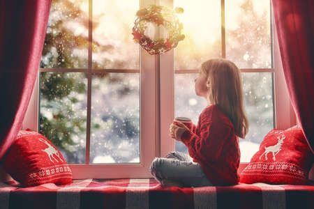 christmas light: Merry Christmas and happy holidays! Cute little girl sitting by the window with a cup of hot drink and looking at the winter forest. Room decorated on Christmas. Kid enjoys the snowfall.
