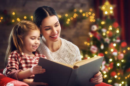 kid book: Merry Christmas and Happy Holidays! Pretty young mom reading a book to her cute daughter near Christmas tree indoors.