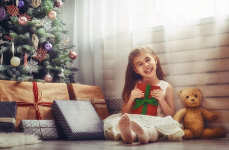 miracle tree: Merry Christmas and Happy Holidays! Cheerful cute little child girl with present. Kid holds a gift box near Christmas tree indoors.