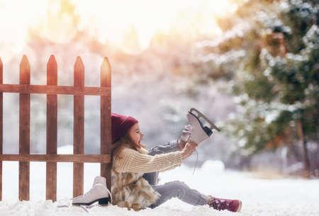 Niño feliz que juega en un paseo de invierno en la naturaleza. Niña linda chico va de patinaje al aire libre. Foto de archivo - 65152572