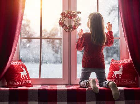 Feliz Navidad y felices fiestas! Niña linda que se sienta junto a la ventana y mirando el bosque de invierno. Habitación decorada en Navidad. Kid disfruta de las nevadas. Foto de archivo - 65389955