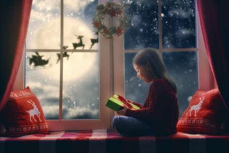 Prettige Kerstdagen en een fijne vakantie! Leuk weinig kind meisje vergadering door raam en kijkt naar de Kerstman die in zijn slee tegen maan hemel. Kamer ingericht op Kerstmis. Kid genieten van de vakantie.