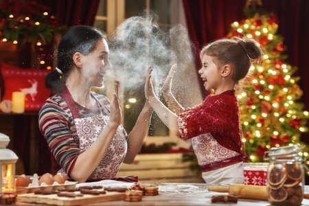 Merry Christmas and Happy Holidays. Family preparation holiday food. Mother and daughter cooking Christmas cookies. 免版税图像