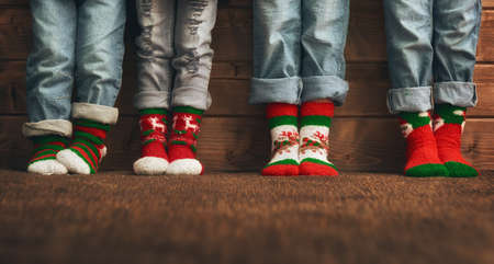 family and friends: Merry Christmas and Happy Holidays. Group of four kids on wooden background. Childrens feet in socks with a Christmas ornament. Red, green and white colors. Stock Photo
