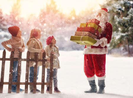 Merry Christmas and Happy Holiday! Cute children girls and boy playing on a winter walk in nature. Happy kids outdoors. Santa Claus presents gifts to nice kids. Stock Photo