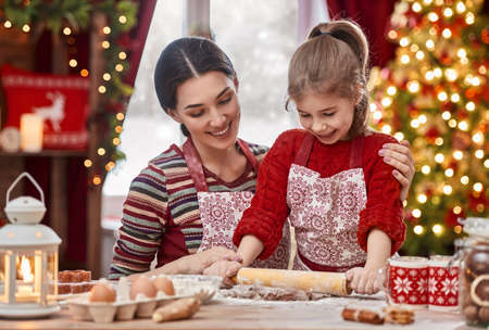 christmas cooking: Merry Christmas and Happy Holidays. Family preparation holiday food. Mother and daughter cooking Christmas cookies. Stock Photo