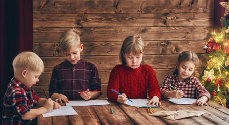 letter writing: Merry Christmas and Happy Holidays. Group of four children on wooden background. Portrait of beautiful cute little kids writing letters to Santa Claus.