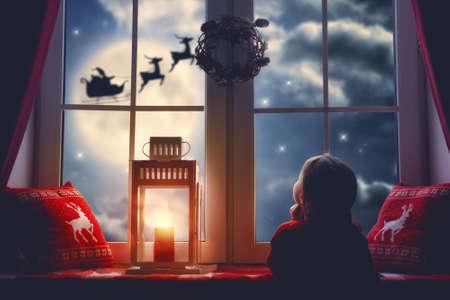 메리 크리스마스와 해피 홀리데이! 귀여운 작은 자식 소녀 창에 의해 앉아 및 달 하늘에 대 한 그의 썰매에 비행 산타 클로스를 찾고. 크리스마스에 꾸