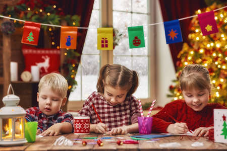 designer baby: Merry Christmas and Happy Holidays. Adorable little children make cards, gifts and decorations for the holiday. Cute kids are engaged in creativity. Stock Photo