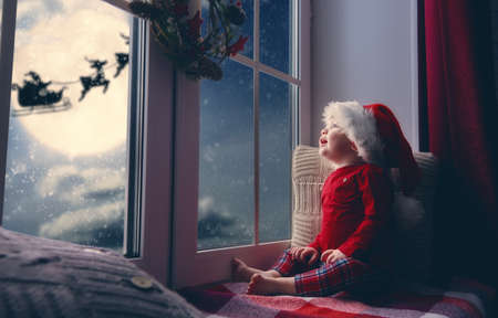Merry Christmas and happy holidays! Cute little child baby girl sitting by window and looking at Santa Claus flying in his sleigh against moon sky. Room decorated on Christmas. Kid enjoy the holiday.