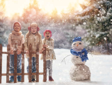 Cute children girls and boy playing on a winter walk in nature. Happy kids outdoors. Stok Fotoğraf - 65390100