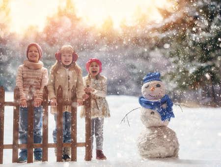 Leuke kinderen meisjes en jongen te spelen op een winterse wandeling in de natuur. Gelukkige jonge geitjes in openlucht.