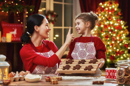 holiday food: Merry Christmas and Happy Holidays. Family preparation holiday food. Mother and daughter cooking Christmas cookies. Stock Photo