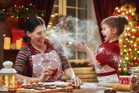 Merry Christmas and Happy Holidays. Family preparation holiday food. Mother and daughter cooking Christmas cookies. Stock Photo