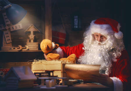 legends: Merry Christmas and Happy Holidays! Santa Clause is preparing gifts for children for Xmas at his desk at home. Christmas legends and traditions. Stock Photo