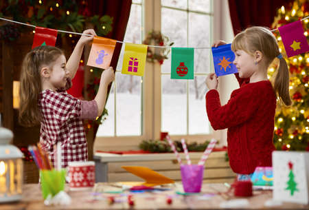 Merry Christmas and Happy Holidays. Adorable little children make cards, gifts and decorations for the holiday. Cute kids are engaged in creativity. Stock Photo