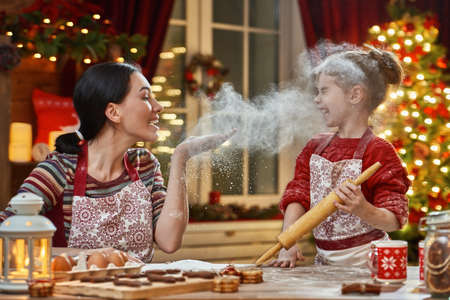 Merry Christmas and Happy Holidays. Family preparation holiday food. Mother and daughter cooking Christmas cookies. Imagens