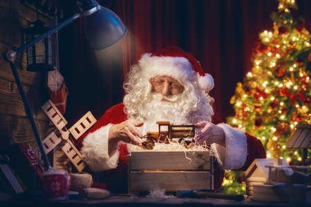 메리 크리스마스와 해피 홀리데이! 산타 절 집에서 자신의 책상에서 크리스마스를위한 어린이위한 선물을 준비합니다. 크리스마스 전설과 전통.