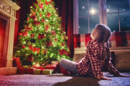 happy christmas: Merry Christmas and Happy Holidays! Cute little child girl looking at decorations the Christmas tree. Christmas family traditions.