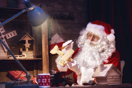 legends: Merry Christmas and Happy Holidays! Santa Claus is preparing gifts for children for Xmas at his desk at home. Christmas legends and traditions.