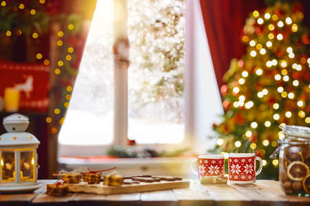 메리 크리스마스와 해피 홀리데이. 가족 티 파티의 시간. 나무 테이블에 크리스마스 쿠키와 따뜻한 녹차의 컵.