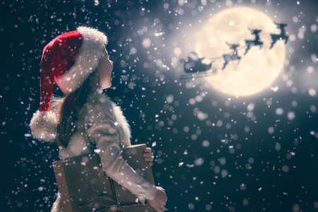 Merry Christmas and happy holidays! Cute little child girl with xmas present. Santa Claus flying in his sleigh against moon sky. Kid enjoy the holiday. Portrait kid with gift on dark background. Stock Photo