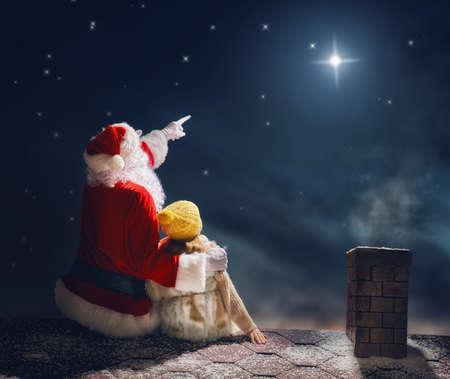 メリー クリスマスとハッピー ホリデー!かわいい小さな子供女の子とサンタ クロース屋根の上に座っているとクリスマスの星を見ています。クリスマスの伝説のコンセプトです。 写真素材 - 65951269