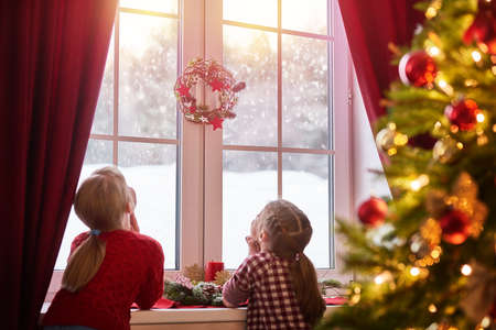 Merry Christmas and happy holidays! Cute little children girls sitting by the window and looking at the winter forest. Room decorated on Christmas. Kids enjoy the snowfall. Imagens