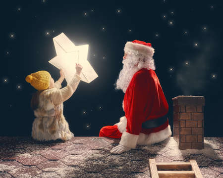 happy christmas: Merry Christmas and happy holidays! Cute little child girl and Santa Claus sitting on the roof and looking at Christmas star. Christmas legend concept.