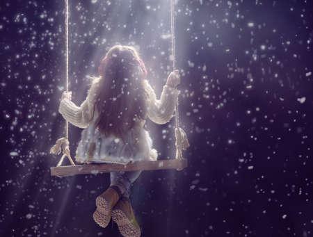 눈 덮인 겨울 산책 행복한 아이 소녀. 어린 소녀는 게임을 즐긴다. 눈에 야외 스윙 연주 자식 소녀. 겨울 휴가를위한 야외 재미. 어두운 배경에 세로 아