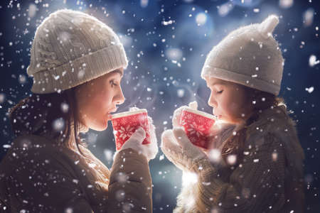 Happy loving family! Mother and child girl drinking tea on snowy winter walk in nature. Frost winter season.