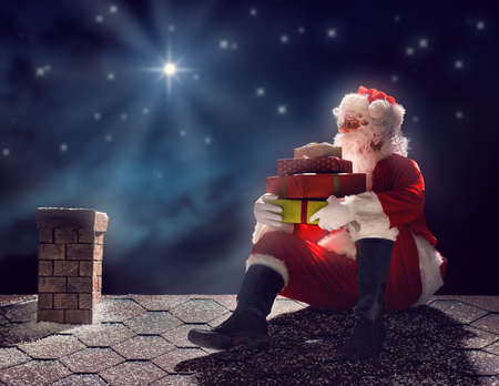 Merry Christmas and happy holidays! Santa Claus sitting on the roof of the house and puts the presents in the chimney. Christmas legend concept. Stock Photo