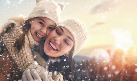 family playing: Happy loving family! Mother and child girl having fun, playing and laughing on snowy winter walk in nature. Frost winter season.
