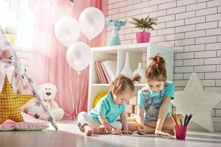 niños felices: Felices los niños juegan. Pequeñas muchachas de los niños dibujan con lápices de colores en el interior. niños encantadores divertidos que se divierten en la habitación de los niños. Hermanas jugando juntos. Foto de archivo