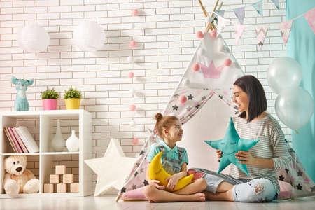 행복 한 사랑 가족. 어머니와 그녀의 딸 여자 어린이 방에서 재생할 수 있습니다. 재미 엄마와 실내 사랑스러운 아이 재미.