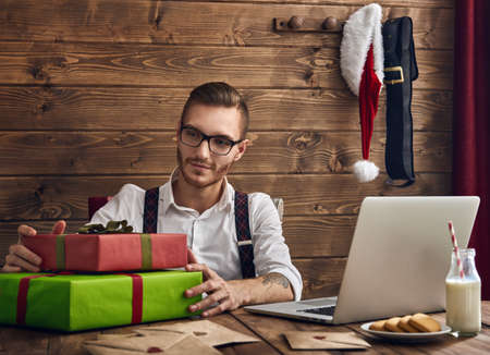 christmas symbol: Merry Christmas and Happy Holidays! Handsome man with Santa symbol. Hipster young Santa Claus concept.