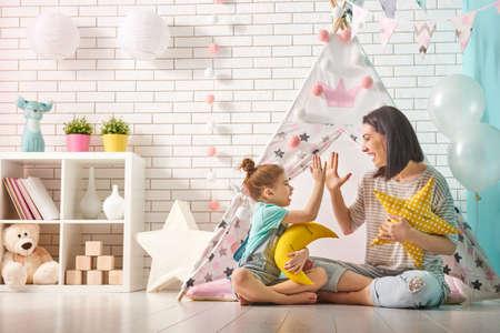Gelukkig liefdevolle familie. Moeder en haar dochter meisje spelen in de kinderkamer. Grappige mamma en mooie kind plezier binnenshuis.