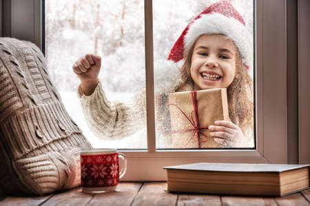 christmas present box: Merry Christmas and happy holidays! Cute little girl looking in window, standing outdoors on winter forest background. Child holding present gift box.