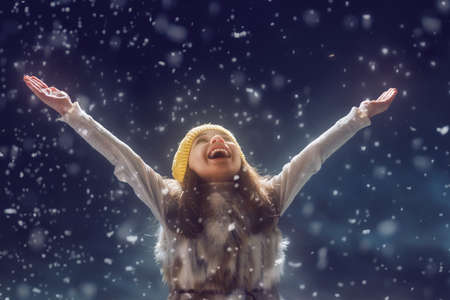 child smile: Happy child girl playing on a snowy winter walk. Little girl enjoys the game. Child girl playing outdoors in snow. Outdoor fun for winter vacation. Portrait kid on dark background.
