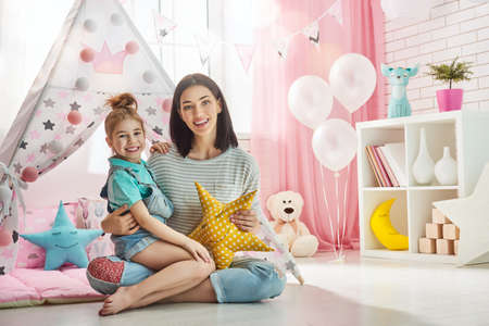 Happy loving family. Mother and her daughter girl play in children room. Funny mom and lovely child having fun indoors. Stock fotó - 66689291