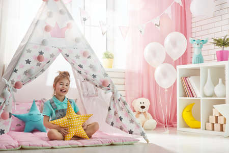 Happy girl play at home. Funny lovely child having fun in children room.