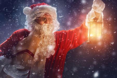 Frohe Weihnachten und schöne Feiertage! Weihnachtsmann-Geschenk und Laterne halten. Standard-Bild - 66689624