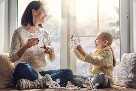 Frohe Weihnachten und schöne Feiertage! Glückliche liebevolle Familie sitzt am Fenster und Herstellung von Papier Schneeflocken für Dekoration Fenster. Mutter und Kind zu schaffen Dekorationen. Standard-Bild - 66689630